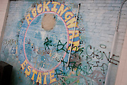 Street mural landscape on the Rockingham Estate in the London borough of Southwark, England. Graffiti has been sprayed on the brickwaork where the mural has been painted near a junction and on the wall of a corner community shop. Rockingham is located in south London near the Elephant and Castle. Notorious for youth issues including gangs and knife crime where 12-year-olds are seen holding knives in broad daylight. For families with young children this would be an intimidating community in which to live.