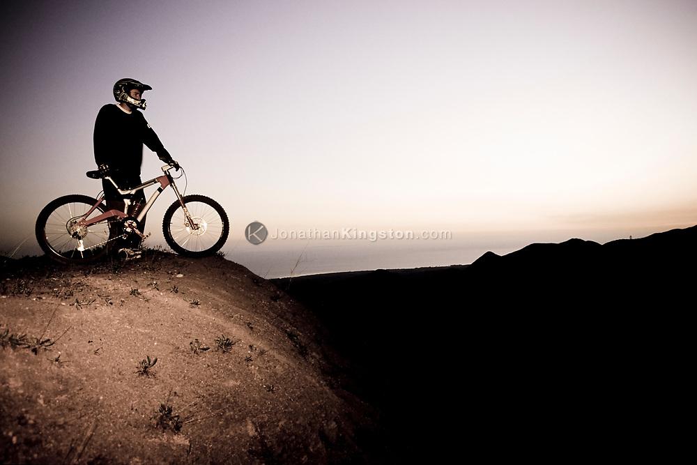 A mountain biker wearing a helmet standing on a hill above the ocean at dusk in Santa Barbara, California.(releasecode: jk_mr1026) (Model Released)