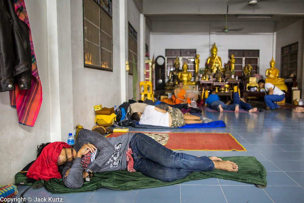 "22 MARCH 2013 - NAKHON CHAI SI, NAKHON PATHOM, THAILAND: People sleep in a common room at Wat Bang Phra during the tattoo festival. Wat Bang Phra is the best known ""Sak Yant"" tattoo temple in Thailand. It's located in Nakhon Pathom province, about 40 miles from Bangkok. The tattoos are given with hollow stainless steel needles and are thought to possess magical powers of protection. The tattoos, which are given by Buddhist monks, are popular with soldiers, policeman and gangsters, people who generally live in harm's way. The tattoo must be activated to remain powerful and the annual Wai Khru Ceremony (tattoo festival) at the temple draws thousands of devotees who come to the temple to activate or renew the tattoos. People go into trance like states and then assume the personality of their tattoo, so people with tiger tattoos assume the personality of a tiger, people with monkey tattoos take on the personality of a monkey and so on. In recent years the tattoo festival has become popular with tourists who make the trip to Nakorn Pathom province to see a side of ""exotic"" Thailand. The 2013 tattoo festival was on March 23.   PHOTO BY JACK KURTZ"