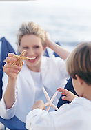 Lifestyle photograph of a young mother holding a starfish, while her young boy brings her another one.