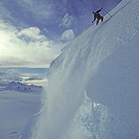 ANTARCTICA, Ski mountaineer Mike Farny jumps icy serac on Mount Berry, Calley Glacier, Danco Coast during Warren Miller ski movie filming.