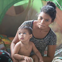 Maria holds her son Isaac under the overpass at Chamelecón, along with hundreds of others her house was washed away and she lost all her belongings.<br /> <br /> Hurricanes Eta and Iota hit hard on the north coast of Honduras, leaving some areas flooded for three weeks, destroying people's furniture, belongings, vehicles and houses as well as standing crops.