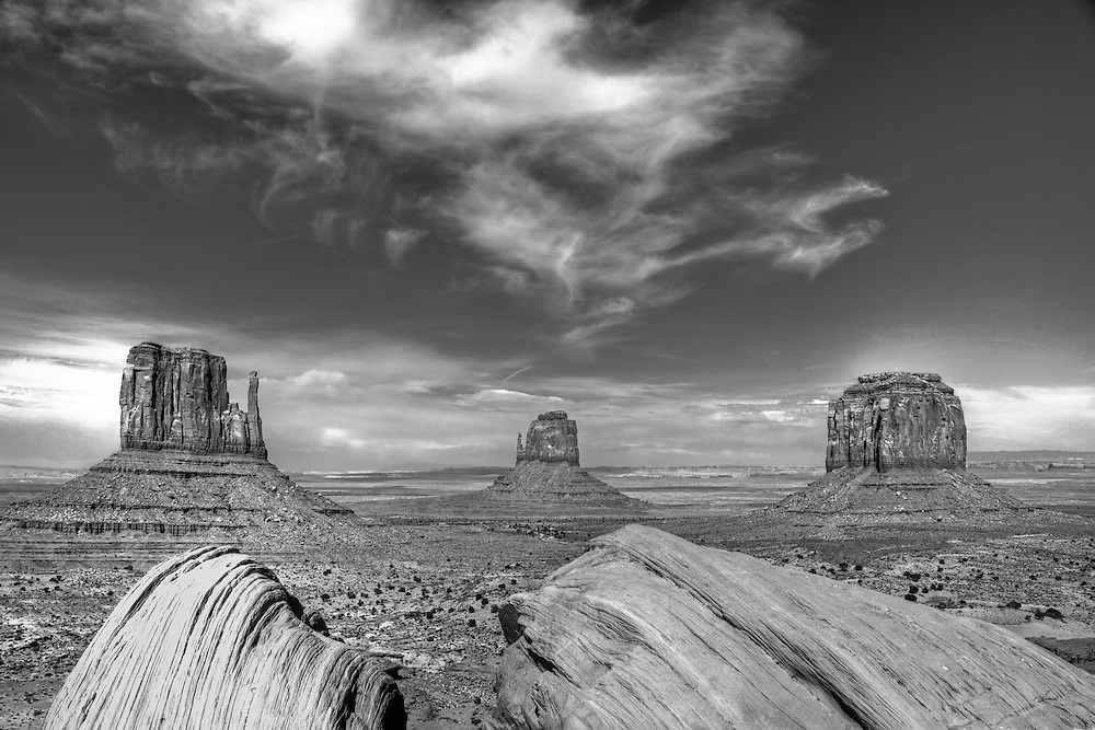 Red Navajo sandstone monoliths rise from the desert near Monument Valley Arizona and Utah.  This black and white treatment enhances the detail in the rocks and contrast between the red sandstone and deep blue afternoon sky.