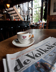 Detail of coffee and local newspaper in old Cafe Het Papeneiland in Jordaan district of Amsterdam in The Netherlands