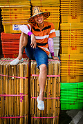A porter taking a break from work, sitting in front of bright, yellow crates, Pak Khlong Talat, Bangkok, Thailand