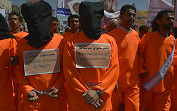 59527275..Yemeni protesters dressed in prison uniforms and in handcuffs attend a rally in front of the U.S embassy in Sanaa, Yemen, on April 16, 2013, demanding the release of prisoners held in Guantanamo prison. Around 90 Yemeni nationals are currently held in the Guantanamo prison, making up the largest part of the remaining detainees at the offshore US facilities, on April 16, 2013, April 17, 2013. Photo by: imago / i-Images. .UK ONLY