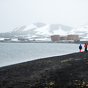 The beach at Whalers Bay, Deception Island, with ruins of the abandoned whaling station in the background. Deception Island, in the South Shetland Islands, is a caldera of a volcano and is comprised of volcanic rock.