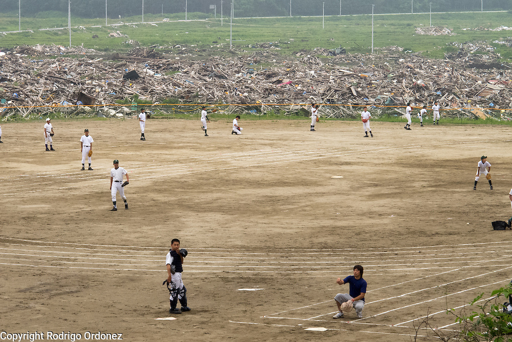 Rubble can be seen on the background as children of Otomo baseball team practice.