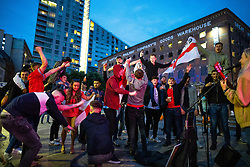 © Licensed to London News Pictures . 18/06/2021. Manchester, UK. Football fans and revellers dance on Peter Street outside the Great Northern Railway Company's Goods Warehouse as a busker plays songs by Manchester band Oasis , following the European Cup tie between England and Scotland at Wembley Stadium . Photo credit: Joel Goodman/LNP