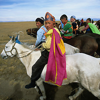 """MONGOLIA, Darhad Valley. Young riders set out for start of a """"naadum"""" (festival) race."""