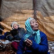 Mongolia. family of Tsatans -reindeer tribe - inside their traditional tent   , ancestor of the american indian tipi . .  during the Ice festival on the frozen Khuvsgul lake. - siberia border - for the mongol new year ,  tsagaan sar, in the cold winter   Khuvsgul province  Khuvsgul province -    / Famille de nomades tsatans. a l interieur de la tente  , ancetre des tipis des indiens d amerique du nord.  Festival des glaces sur le lac gelé de Khovsgol - frontiere siberienne-  pour Tsagan sar; le nouvel an mongol, en hiveir dans le froid   Khovgul  -    Khovgul  - Mongolie   / L0055887B