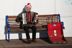 © Licensed to London News Pictures. 24/12/2014. Southsea, Hampshire, UK. A busker playing christmas songs in remembrance of Mike Bell, a member of a local church who helped homeless people today, Christmas Eve, in Southsea, Hampshire. Photo credit : Rob Arnold/LNP