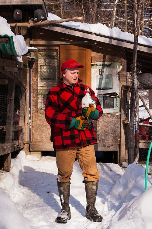 A portrait of a farmer looking affectionately at a guinea hen in front of a chicken coop on a winter's day.