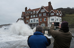 © Licensed to London News Pictures. <br /> 21/03/2015. <br /> <br /> Sandsend, North Yorkshire.<br /> <br /> Members of the public take pictures as huge waves crash against the sea wall at Sandsend in North Yorkshire. The exceptionally high Spring tides were created by the moon's 18-year cycle.<br /> <br /> Photo credit : Ian Forsyth/LNP