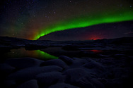 Breathtaking congregation of five elements of nature at Jökulsárlón Glacier Lagoon - Milky Way, Aurora Borealis, Glacier Lagoon, Shooting Star and Holuhraun Volcano eruption glow from a distance. A sight to behold!