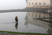 A man searches for octopus in the small pond left by the low tide, near Bele'm Tower. The area of Belem's Tower attracts lots of visitors, both tourists and locals, because of its beauty and peacefulness. Belem's Tower was built in the fifteenth century (1514-1520) as a military fortification. It was recognized as a UNESCO World Heritage Site in 1983.