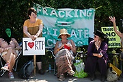 Four local anti-fracking women demonstrate their opposition on the pavement outside the gates in New Preston Road, Lancashire, United Kingdom, June 29th 2018.  Block Around the Clock - a fourty eight hours of event with work shops, yoga, sleeping and anti-fracking campaigning in front of the gates to Cuadrillas fracking site in Lancashire. The event was organised by anti-fracking campaigners in spite of an injunction granted to Cuadrilla to prevent protest against the impending shale gas exploitation. The Cuadrilla site in Lancashire in a highly contested site, almost ready to drill for gas.