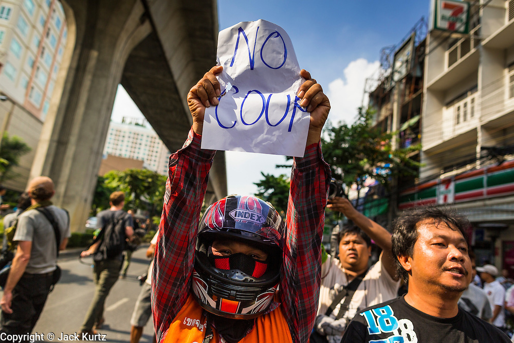 24 MAY 2014 - BANGKOK, THAILAND: A Thai anti-coup protestor holds up a sign during a march in Bangkok. There were several marches in different parts of Bangkok to protest the coup that unseated the popularly elected government. Soldiers and police confronted protestors and made several arrests but most of the protests were peaceful. The military junta also announced that firing of several police commanders and dissolution of the Thai Senate. The junta also changed its name from National Peace and Order Maintaining Council (NPOMC) to the National Council for Peace and Order (NCPO).   PHOTO BY JACK KURTZ