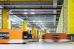 "© Licensed to London News Pictures . 04/12/2019. Manchester , UK . Robotic stock trucks move around inside a secured area within the ""MAN1"" Amazon fulfilment centre warehouse at Manchester Airport in the North West of England . Photo credit : Joel Goodman/LNP"