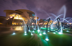 Night view of the new National Museum of Qatar  with illuminated fountains in Doha , Qatar. Architect Jean Nouvel.