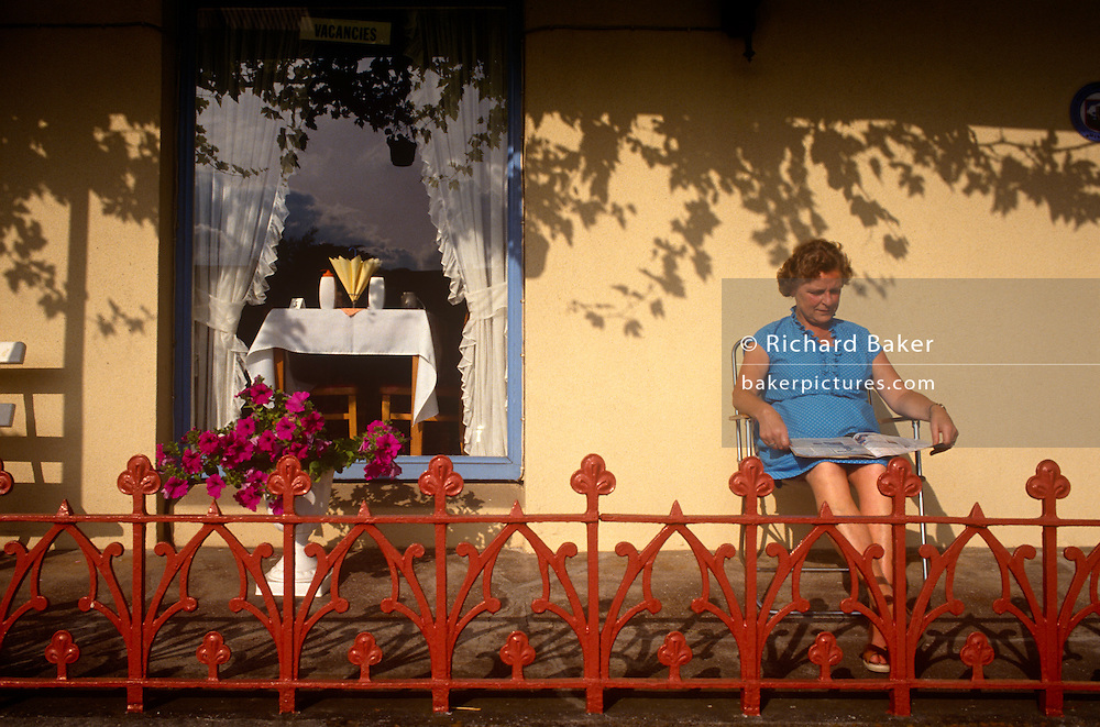 A lady sits outside in morning sunshine on the terrace of her B+B guesthouse in the Devon seaside town of Paignton. It is late morning and a lady has emerged from her bead and breakfast. Sunlight is quite high in the sky and the shadows of a vine that is growing across the roof of the building's terrace, is seen on the wall behind the woman. She is seated reading a magazine in a garden chair and is surrounded by colourful flowers in their prime. Well-painted original victorian railings that act as a sort of ballustrade are in front of the female. In the window is a scene of typical seaside Englishness. Serviettes are splayed out on a table along with breakfast or dinner items awaiting guests at the next meal.