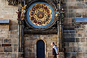 A man wearing a face mask passing the Astronomical clock at Old Town Square in Prague. As of 21st of October 2020 people have to wear face masks outside and inside.