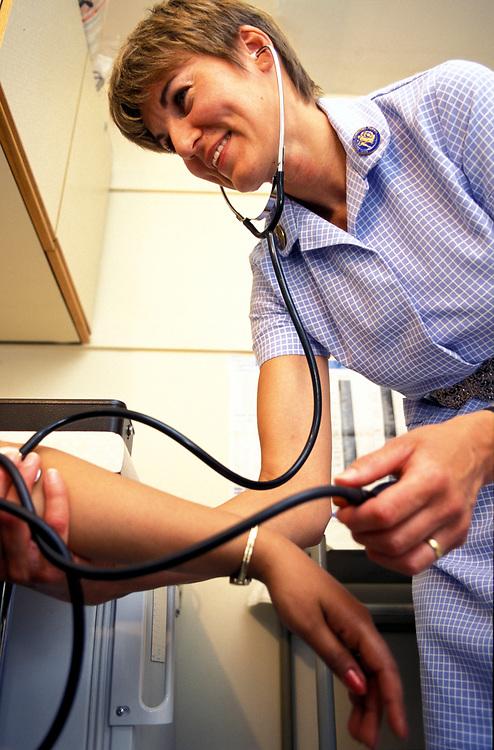 Practice nurse taking blood pressure of patient,