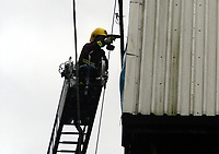 Picture: Henry Browne.<br />Date: 31/01/2004.<br />Crystal Palace v Wimbledon Nationwide Division One.<br /><br />A Fireman tries to  secure the roof of one of the stands at  Selhurst Park that was affected by the wind.
