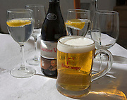 Beer and iced water glasses and wine bottle on restaurant table in Spain
