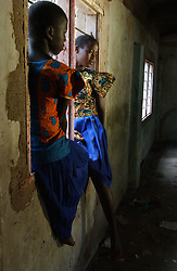 Shinyanga, Tanzania, October 4, 2003: Girls who have just finished exams for 7th Standard, Eunice Sospeter, left and her friend Helena Simon sit in a window October 04, 2003 in Shinyanga, Tanzania. (Photo by Ami Vitale)