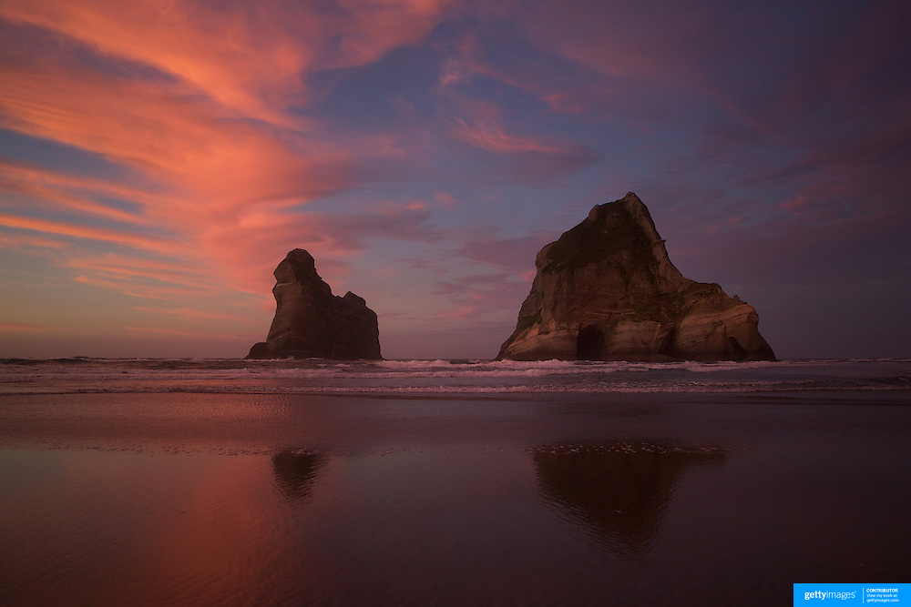 Sunset at Wharariki Beach and Archway Islands, Golden Bay, situated just west of Cape Farewell and Farewell Spit at the northern most point of the South Island of New Zealand..Wharariki beach is approximately an hour's drive from Takaka, and is accessible by a 20 minute stroll across private, rolling farmland..The remote beach is characterised by bold cliff lines, high arches, caves, sand dunes and is home to fur-seals and seabirds. The wind sweeping the western coast has resulted in quirky, intriguing bushland. Wharariki Beach, South Island, New Zealand. 7th February 2011. Photo Tim Clayton..