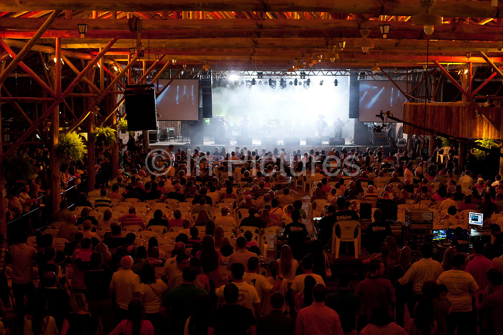 Crowd shot of medium to large music event, view from rear with smoke and lighting on stage, country music, Reponte da Cancao music festival and song competition in Sao Lorenzo do Sul, RIo Grande do Sul, Brazil.