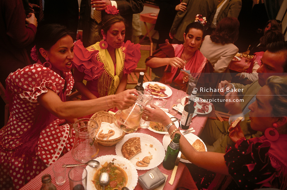 Spanish ladies feast at a private party in a marquee called a Caseta during the annual Feria de Abril, on 11th June 1999, in Seville, Andalucia, Spain. Rows of temporary marquee tents, or casetas, host families, corporations and friends into the late hours during the April Fair which begins begins two weeks after the Semana Santa, or Easter Holy Week in the Andalusian capital.