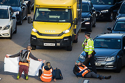 Ockham, UK. 21st September, 2021. Insulate Britain climate activists block the anticlockwise carriageway of the M25 between Junctions 9 and 10 as part of a campaign intended to push the UK government to make significant legislative change to start lowering emissions. Both carriageways were briefly blocked before being cleared by Surrey Police. The activists are demanding that the government immediately promises both to fully fund and ensure the insulation of all social housing in Britain by 2025 and to produce within four months a legally binding national plan to fully fund and ensure the full low-energy and low-carbon whole-house retrofit, with no externalised costs, of all homes in Britain by 2030.
