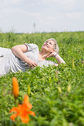 Mature woman lying in grass, smiling