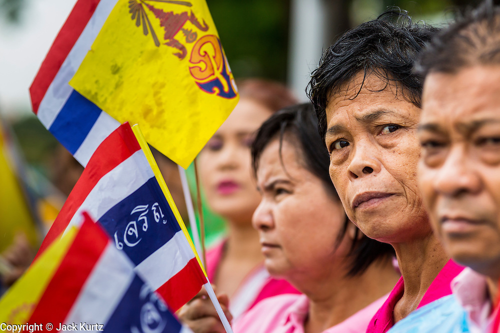 """05 MAY 2013 - BANGKOK, THAILAND:   Thais hold the Thai flag and King's flag while they wait to see Bhumibol Adulyadej, the King of Thailand, Sunday. The King and Queen, who are both hospitalized and in poor health, did not attend Sunday's event. May 5 marks the 63rd anniversary of the Coronation of His Majesty King Bhumibol Adulyadej. The day is celebrated as a national holiday; since this year it falls on a Sunday, it will be observed on Monday May 6, and as such all government offices and commercial banks will close for the day. HM King Bhumibol Adulyadej is the longest reigning monarch in the world. Each year on the 5th of May, the Kingdom of Thailand commemorates the day when, in 1950, the Coronation Ceremony was held for His Majesty King Bhumibol Adulyadej, the 9th in the Chakri Dynasty (Rama IX). On the 5th of May, His Majesty conducts a merit making ceremony, presenting offerings to Buddhist monks, and leads a """"Wien Thien"""" ceremony, walking three times around sacred grounds at the Temple of the Emerald Buddha.    PHOTO BY JACK KURTZ"""