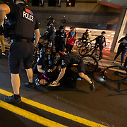 CHARLOTTE, NC - August 23:  A protestor with Charlotte Uprising is immobilized and detained by bike officers with Charlotte-Mecklenburg police for a third night in a row as they protestors marched through uptown Charlotte near the site of the 2020 Republican National Convention in uptown Charlotte on August 23, 2020. The group, organized by Charlotte Uprising is protesting the existence of the convention in Charlotte, the policies of the Trump administration and the the abolishment of police and prisons. Delegates are holding private meetings inside the convention center ahead of the official start of the paired down convention on August 24th. (Photo by Logan Cyrus for AFP)