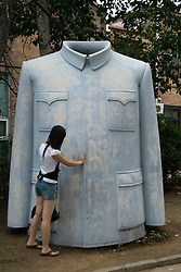 Woman looking at sculpture of a Chairman Mao jacket at Art District 798 in central Beijing a cuting edge venue for contemporary arts