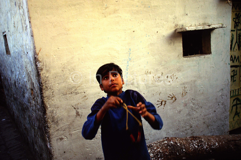 A boy shoots his catapult at birds. Shadipur Depot. Shadipur Depot, New Delhi, India<br /> The Kathiputli Colony in the Shadipur Depot slum is home to hundreds of (originally Rajasthani) performers. The artistes who live here - from magicians, acrobats, musicians, dancers and puppeteers are often international renowed by always return to the Shadipur slum.