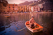 A fisherman rows to the shore in Sorento Italy.