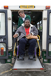 Driver using electronic lift ramp to help wheelchair user onto the mini bus,