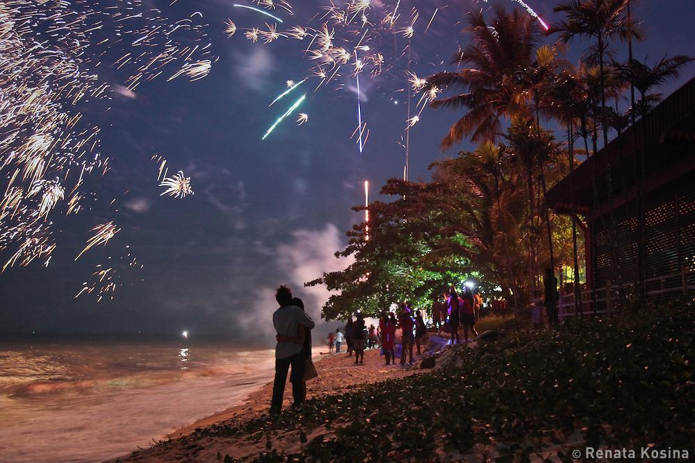People enjoy fireworks and celebrate New Year on a beach in Batu Ferringhi on Penang, Malaysia.