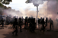 Police confront demonstrators with tear gas and batton charges outside the centre of Genoa, Italy. Banks, shops and cars were burnt and looted. The historic centre of the town had been sealed off for the G8 Summit. Up to 40 % of the city's population left the city and 15,000 police and army personnel sealed off the historic centre in anticipation of violent demonstrations. Up to 100,000 demonstrators protested against global capitalism and world poverty during the summit.
