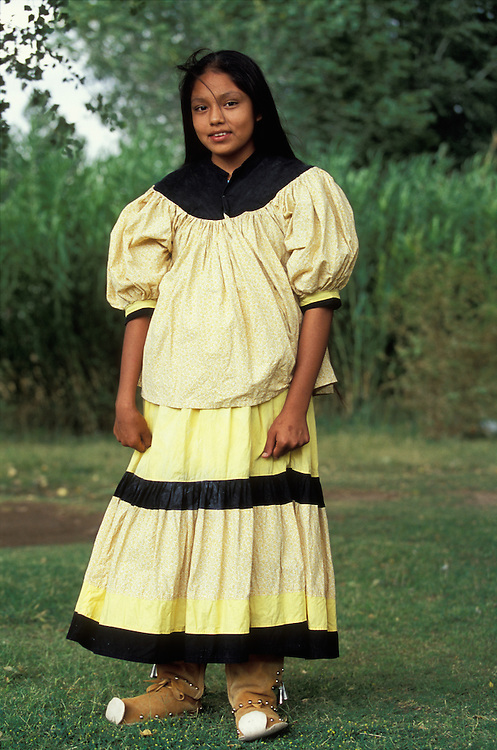 An Apache girl dressed in  camp dress and moccasins on the San Carlos Apache Indian Reservation in Arizona, USA. June 2004.