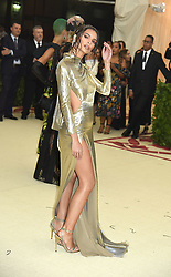 Emily Ratajkowski in gold dress  attends the Costume Institute Benefit at the Metropolitin Museum of Art at the opening of Heavenly Bodies: Fashion and the Catholic Imagination on May 7, 2018 in New York, New York, USA.