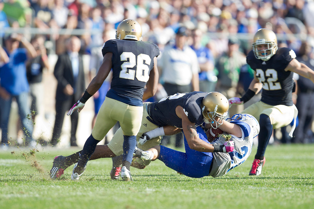 Notre Dame safety Harrison Smith (#22) tackles Air Force fullback Mike DeWitt (#25) in action during NCAA football game between Notre Dame and Air Force.  The Notre Dame Fighting Irish defeated the Air Force Falcons 59-33 in game at Notre Dame Stadium in South Bend, Indiana.