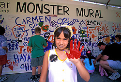 Stock photo of a girl working on the Monster Mural showing her hand covered with paint