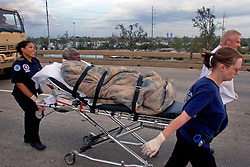 29 August, 2005. New Orleans, Louisiana.<br /> Hurricane Katrina hits New Orleans. Rescue workers frantically search for survivors in the rising flood waters of the 9th ward, bringing them to relevant safety on the elevated section of I-10.  An elderly resident of the 9th ward rescued from his submerged home is immediately transported onto Interstate 10 and waiting paramedics.<br /> Photo; Charlie Varley.