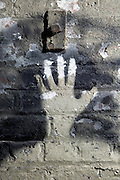 old paint peeling brick wall with spray painted hand imprint