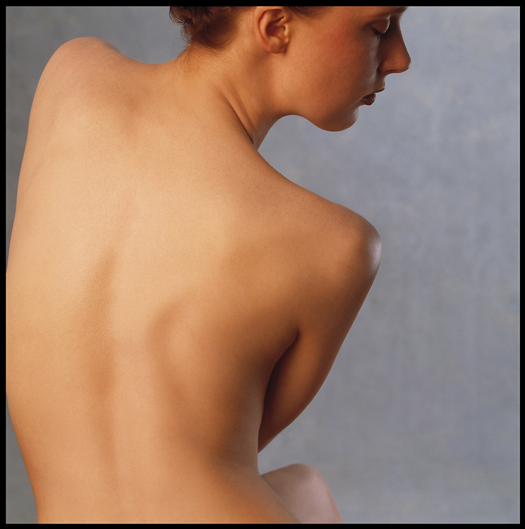 Skincare photo of nude woman's flawless back with profile of her face